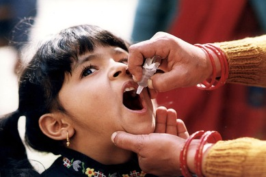 A young girl receiving an oral vaccine for polio. Source: CDC Global