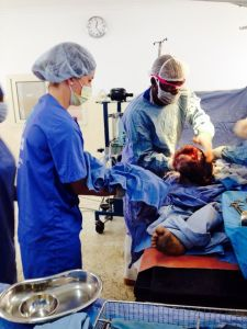 Receiving a baby during a Caesarian section in the obstetrics and gynecology department at Iringa Regional Hospital.