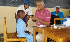 In Kenya, a deaf child is examined by a physician with the help of an interpreter. Source: Flickr user Community Eye Health