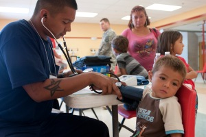 Ruperto Peña receives a blood pressure test from a local Rio Grande Firefighter during Operation Lone Star at Ringgold Middle School in Rio Grande City, Texas, July 30, 2013. Operation Lone Star serves as the only access many residents in the South Texas Border Region have to medical care or doctors.  Available services included immunizations, diabetic and blood pressure screenings, hearing and vision exams, sports physicals and dental services. (U.S. Army National Guard photo by Army Spc. Aaron Moreno) 130730-Z-QF937-369