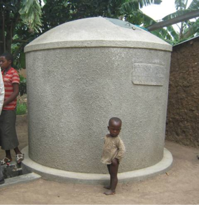 A child stands next to a rainwater tank full of stationary water. Source: Water Journalists Africa.